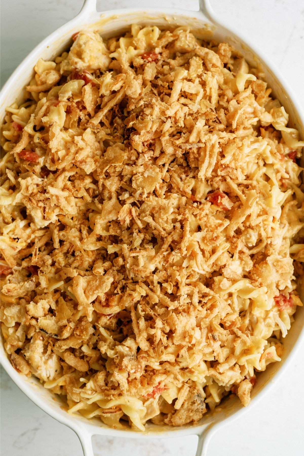 Unbaked French Onion Chicken Noodle Casserole in a white casserole dish