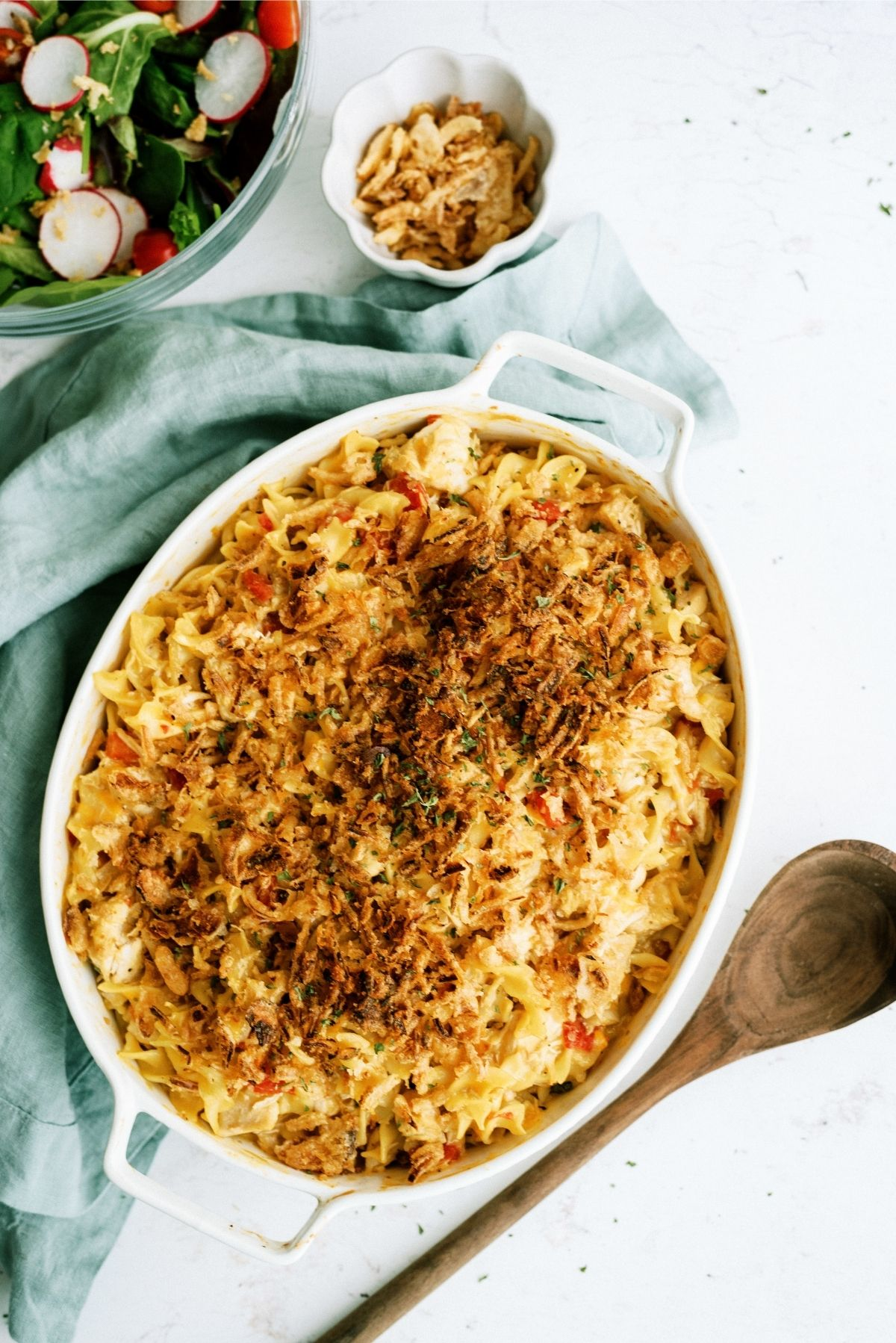 French Onion Chicken Noodle Casserole in a white casserole dish with a wooden spoon and bowl of side salad