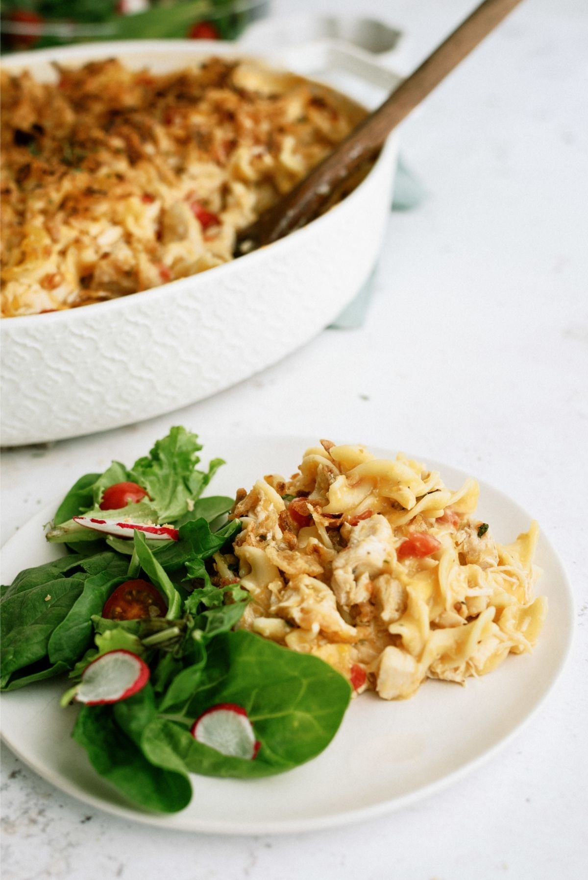 French Onion Chicken Noodle Casserole on a plate with a side salad