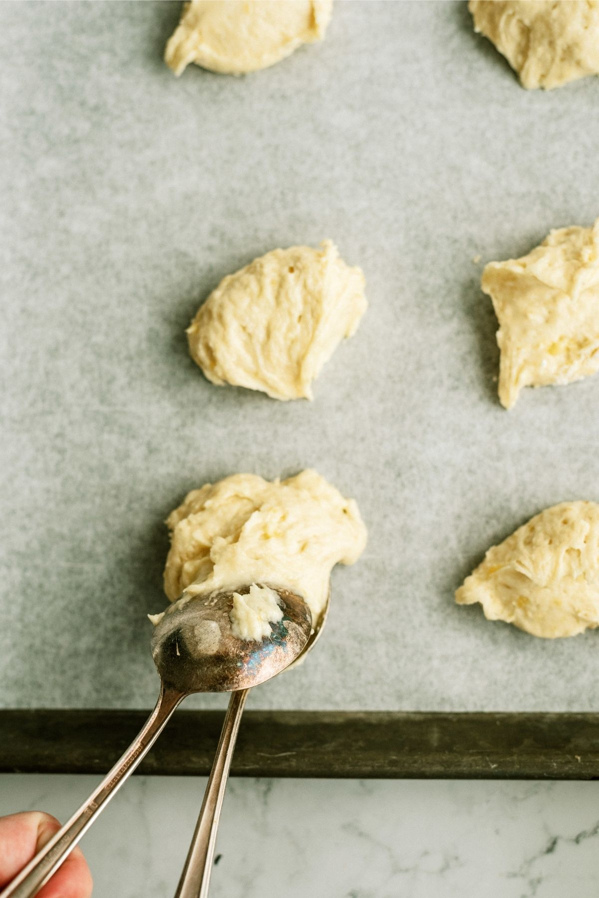 Dropping Cookie batter on baking sheet using table spoons