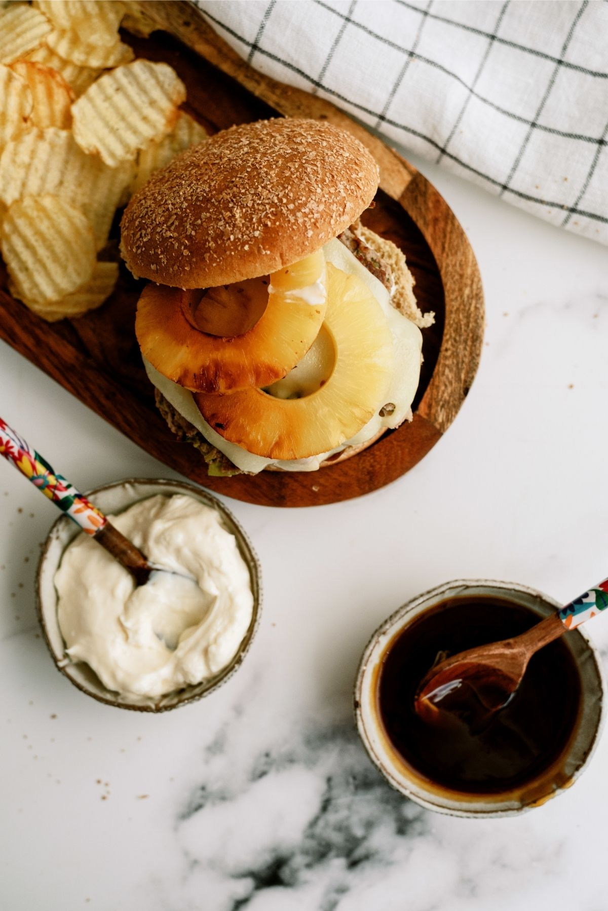 Hawaiian Turkey Burger on wooden plate with chips and sauce