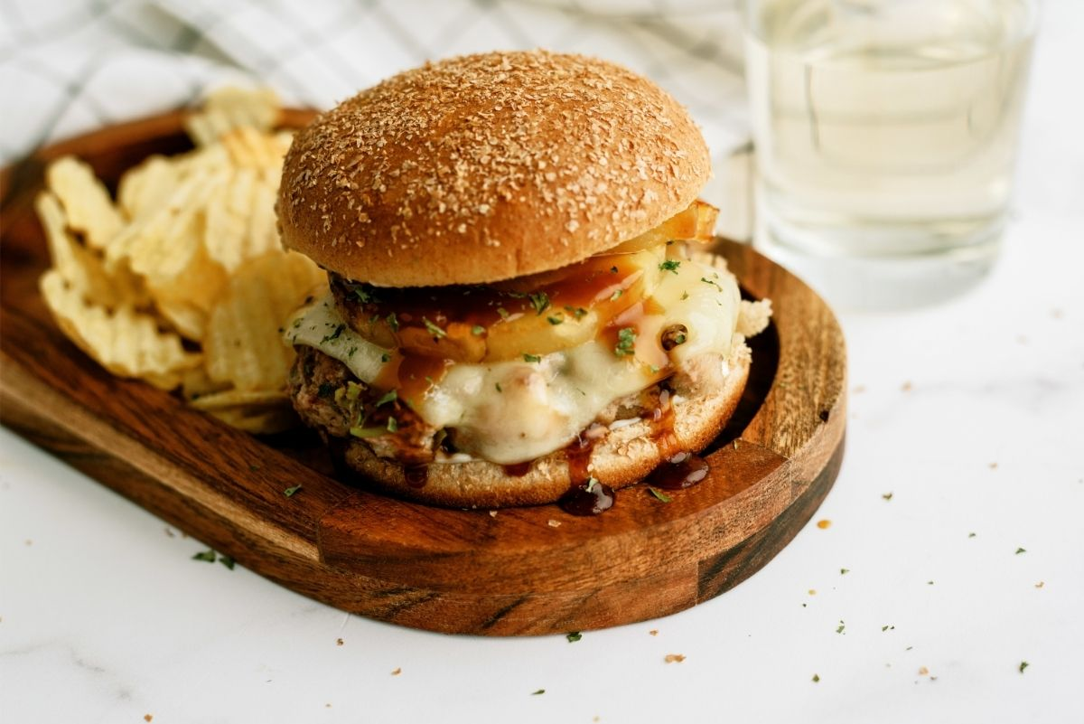 Hawaiian Turkey Burger on a wooden plate with chips