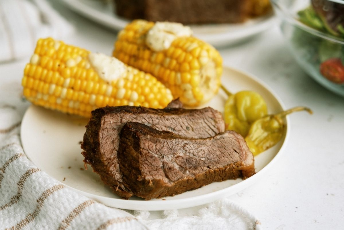 Instant Pot Mississippi Pot Roast sliced on a white plate with corn on the cob and pepperoncini peppers