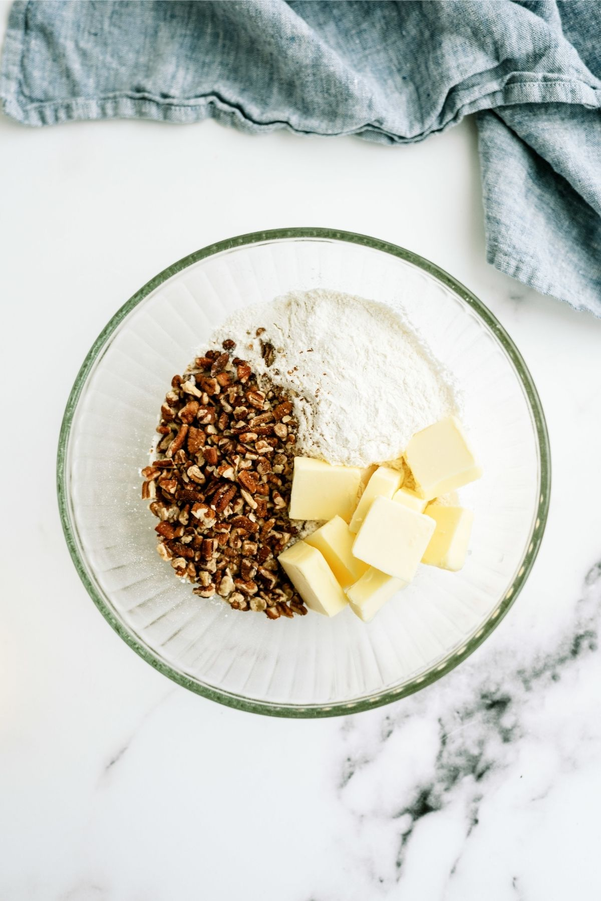 medium-sized mixing bowl with flour, ½ of the chopped pecans, and the softened butter