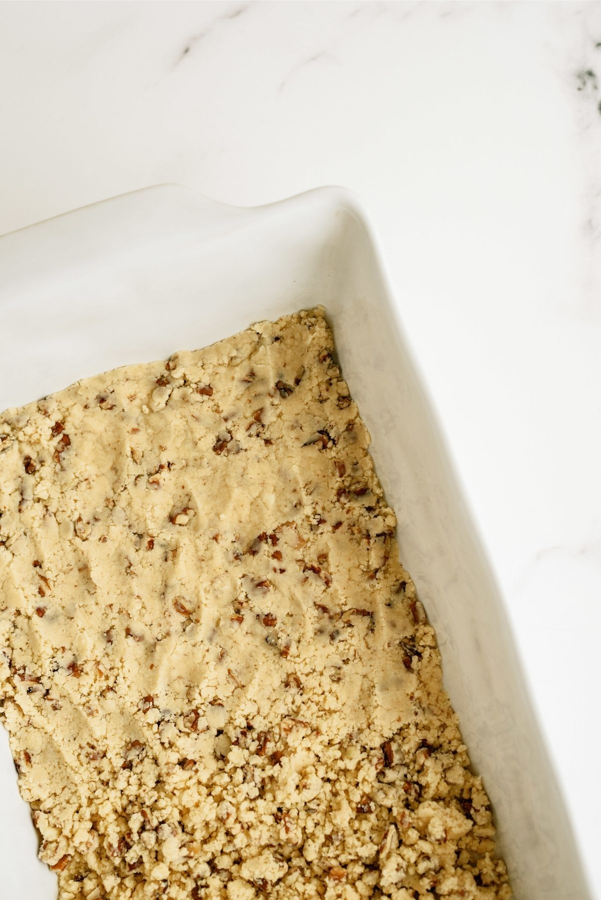 Pecan and flour mix pressed into a baking dish