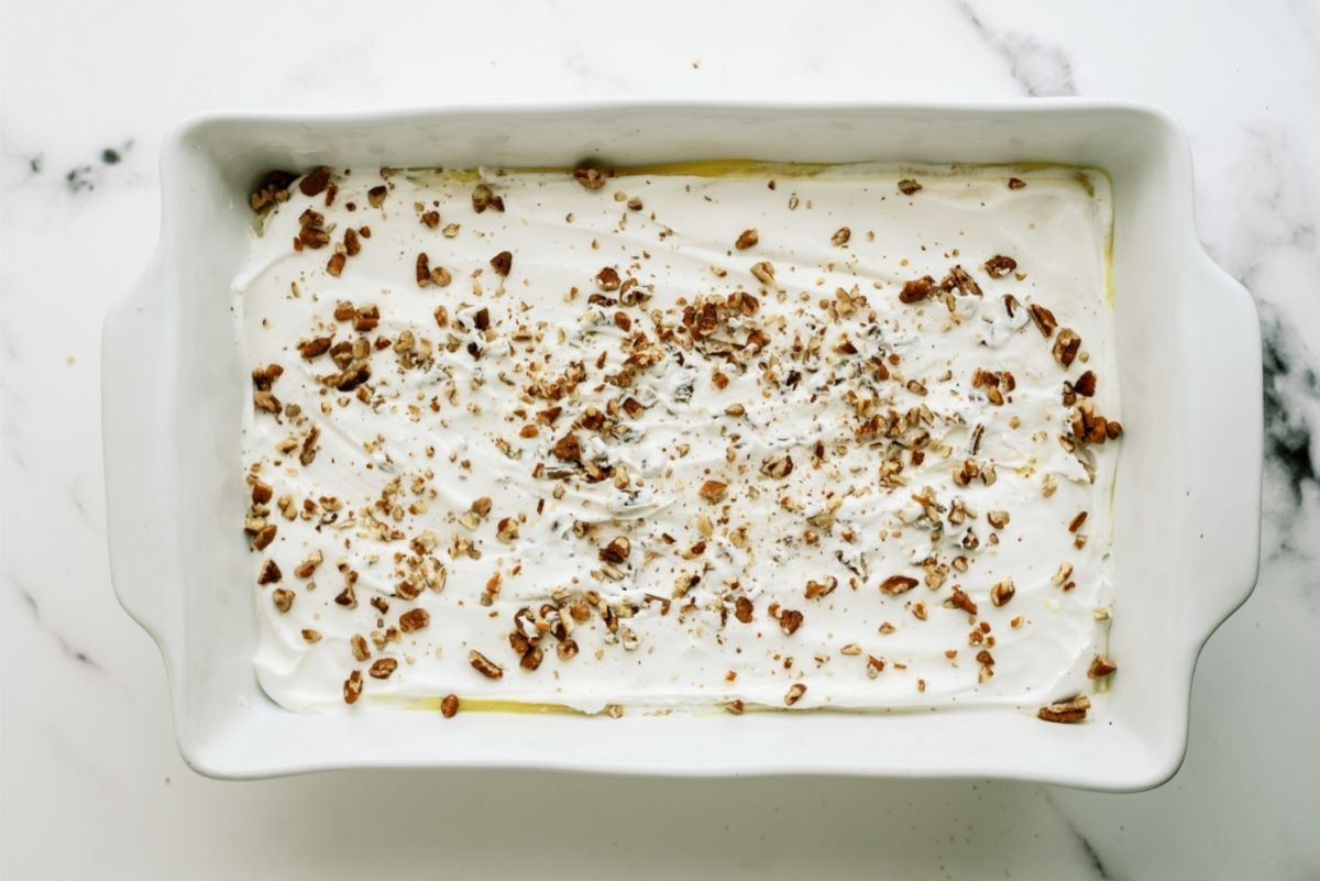 Layered Lemon Dessert with pecans sprinkled on top in baking dish