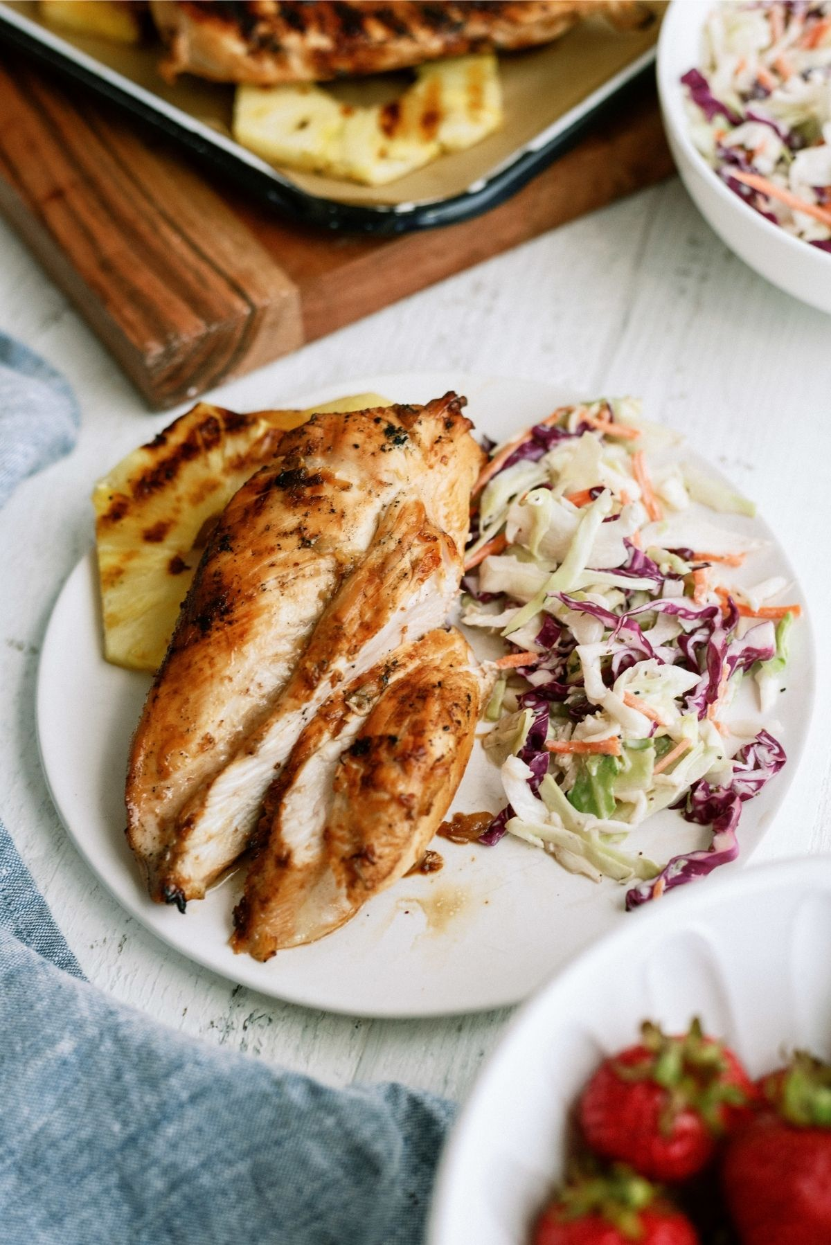 Pineapple Grilled Chicken sliced on a plate served with pineapple and coleslaw