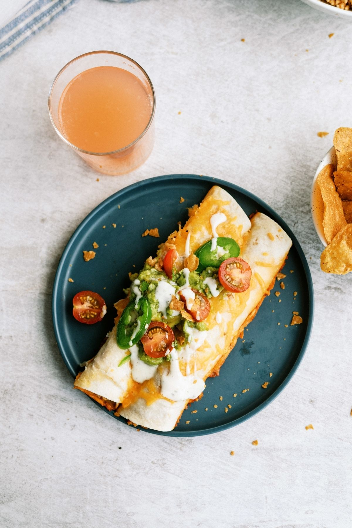 Slow Cooker Ranch Chicken Enchiladas on blue plate with a drink