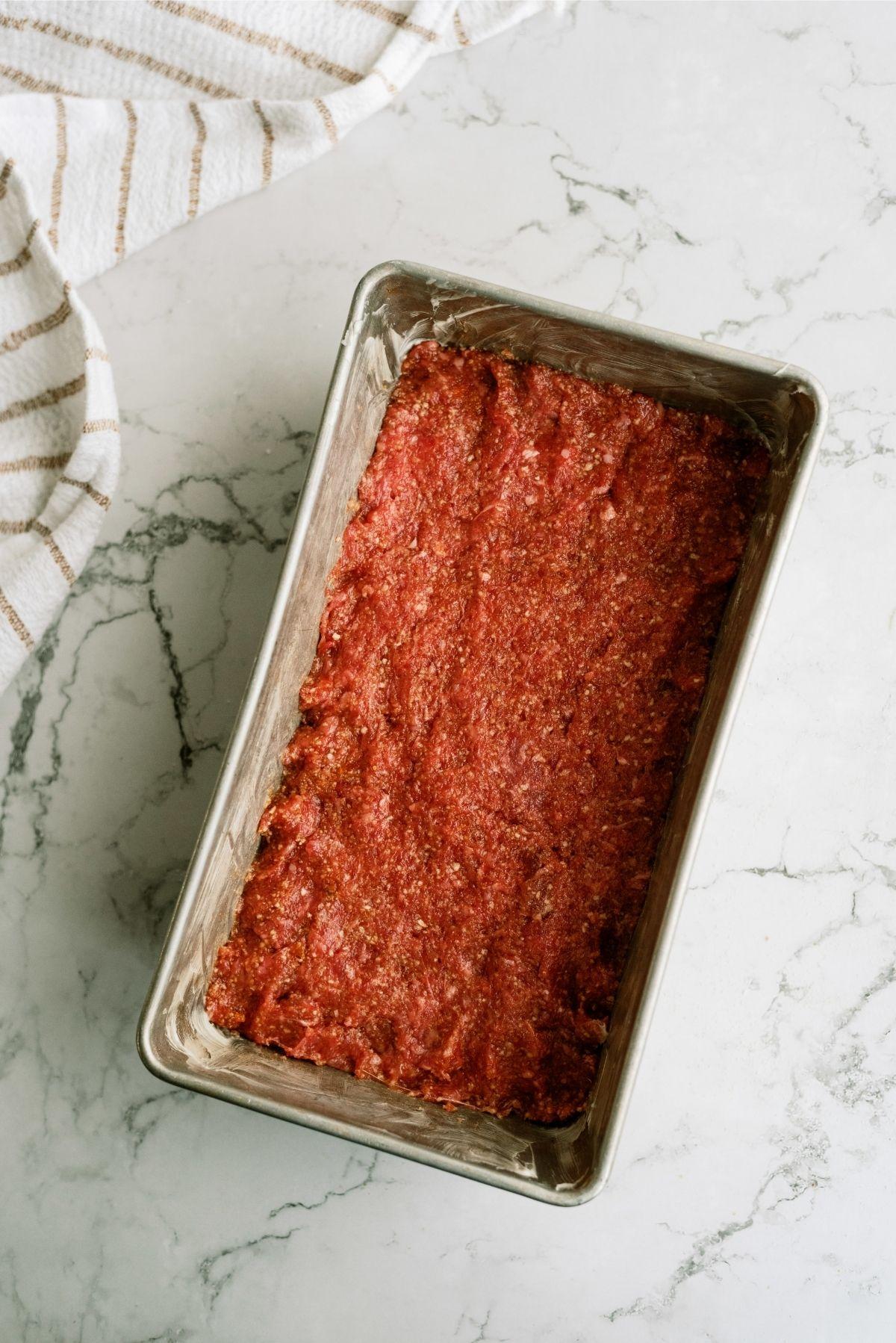 Meatloaf mixture pressed into a loaf pan