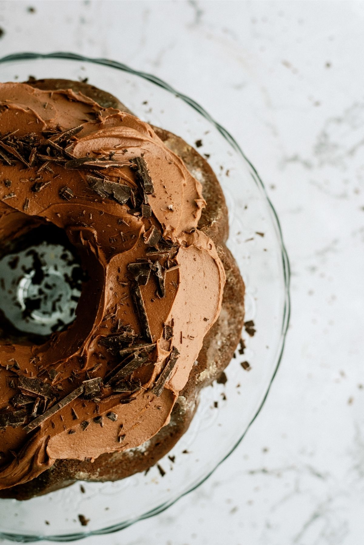 Triple Chocolate Bundt Cake frosted on a glass cake stand