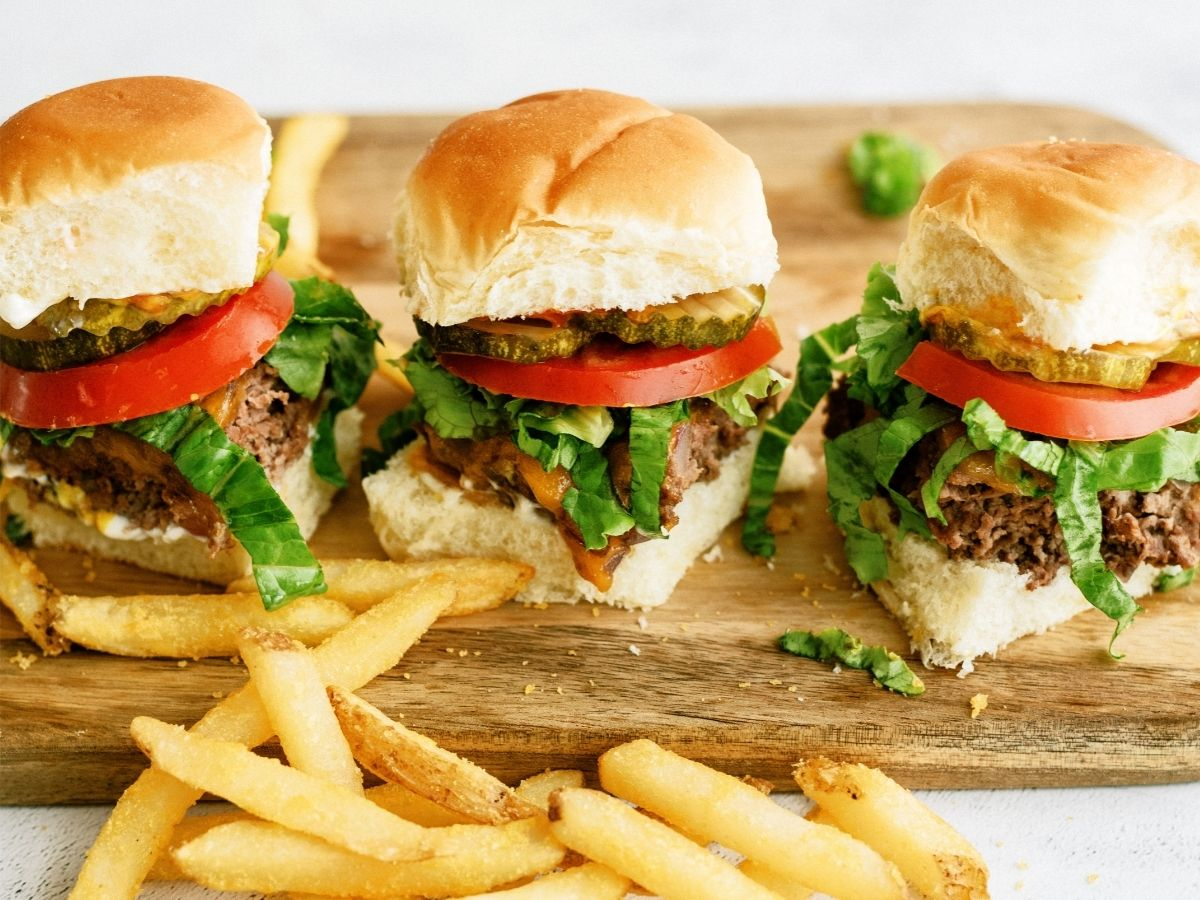 3 Baked Cheeseburger Sliders in a row on a cutting board with fries