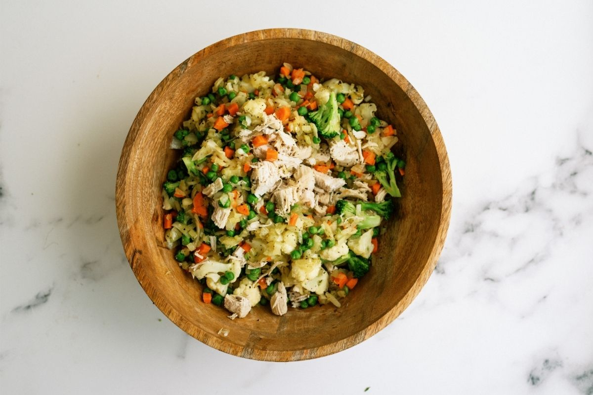Cooked chicken and vegetables mixed in a wooden bowl