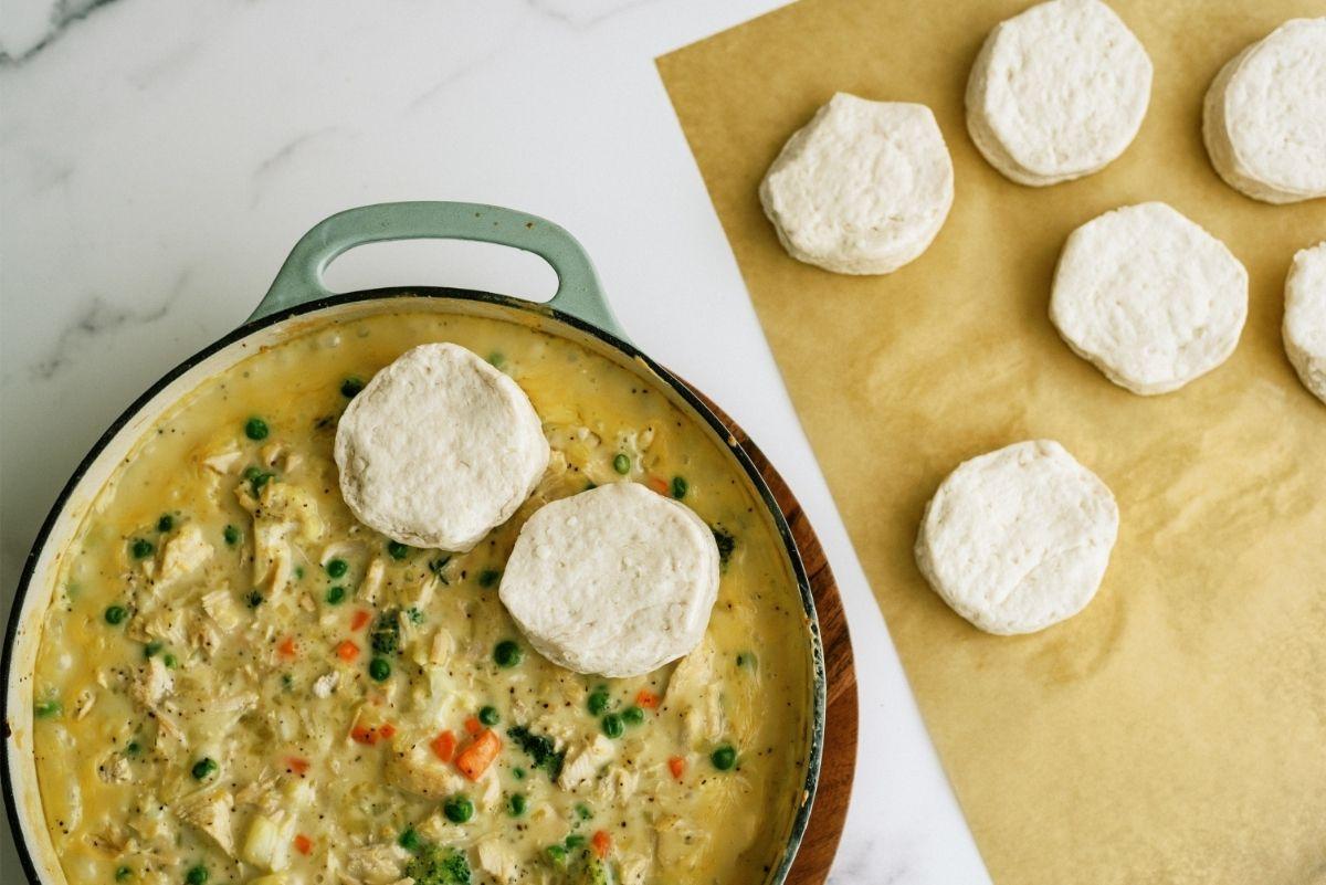Placing uncooked biscuits on top of Pot Pie mixture