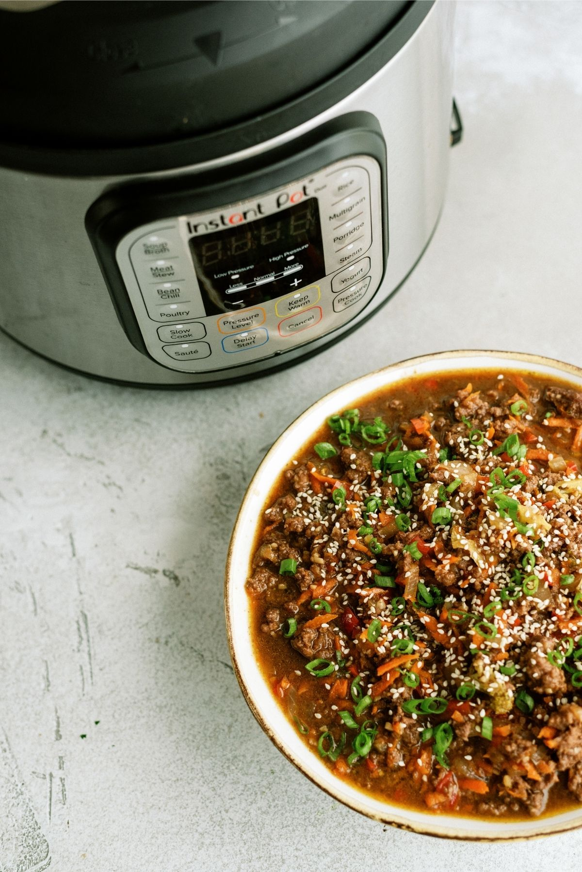 Instant Pot Ground Turkey Teriyaki Rice Bowl with an Instant Pot in the back ground