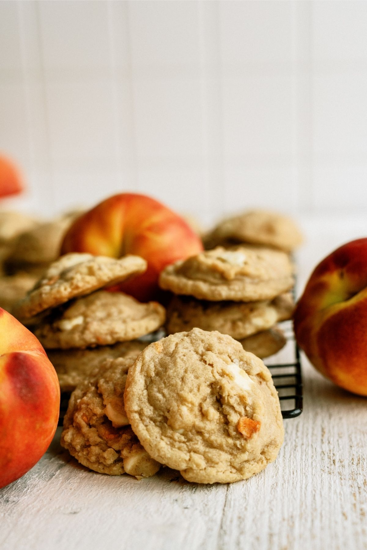 Peaches and Cream Oatmeal Cookies on cooling rack surrounded by fresh pizza