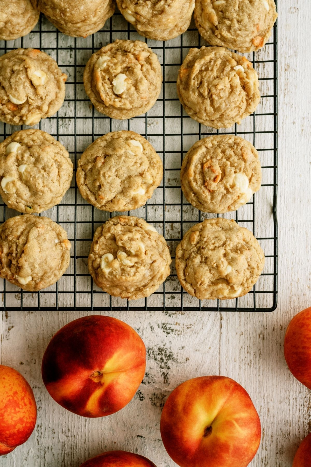 Peaches and Cream Oatmeal Cookies on a cooling rack with fresh peaches