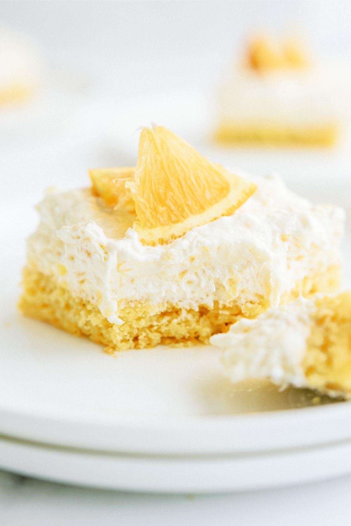A slice of Pineapple Orange Cake Recipe (Pig Pickin' Cake) on stacked white plates