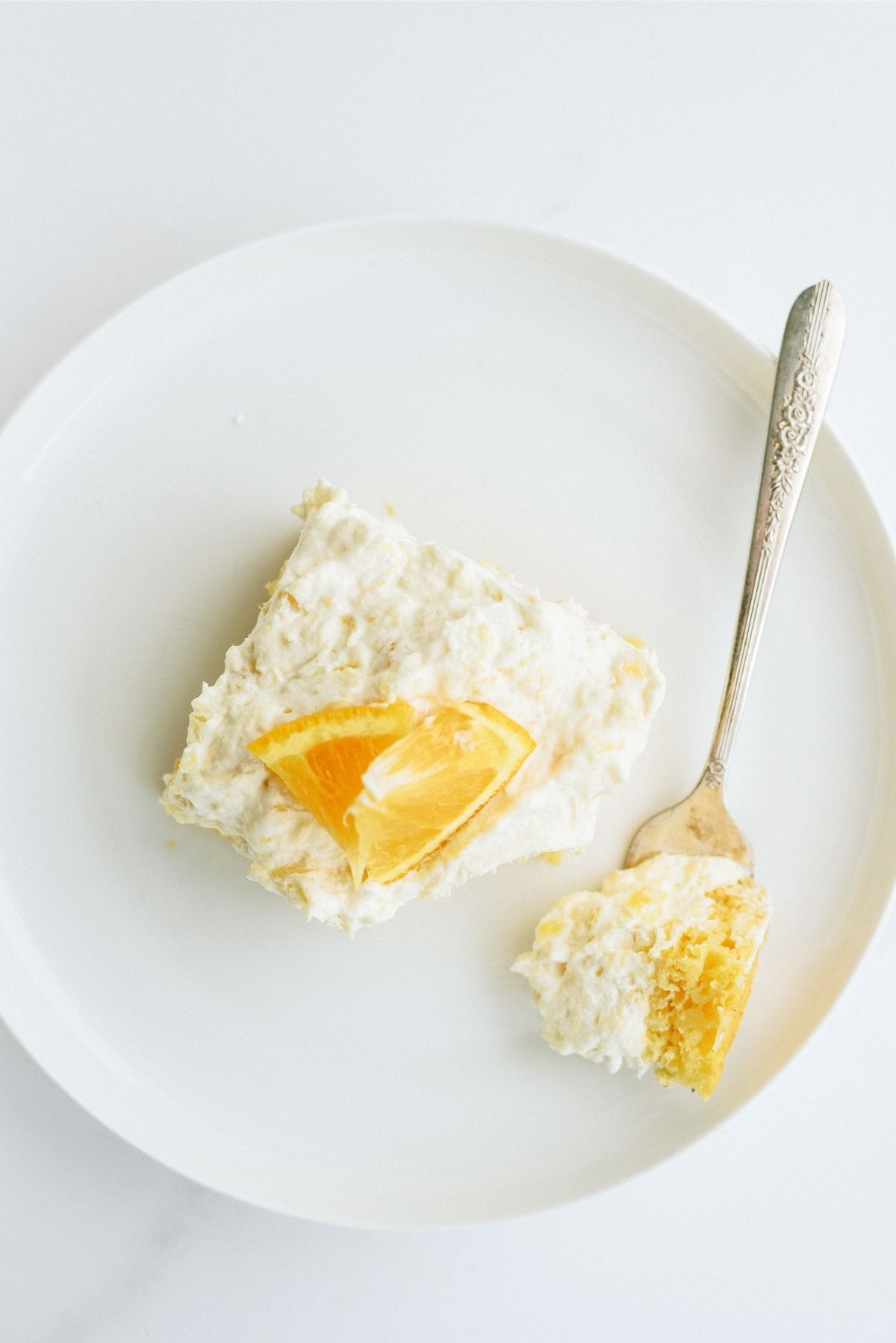 A slice of Pineapple Orange Cake Recipe (Pig Pickin' Cake) on a white plate with a fork