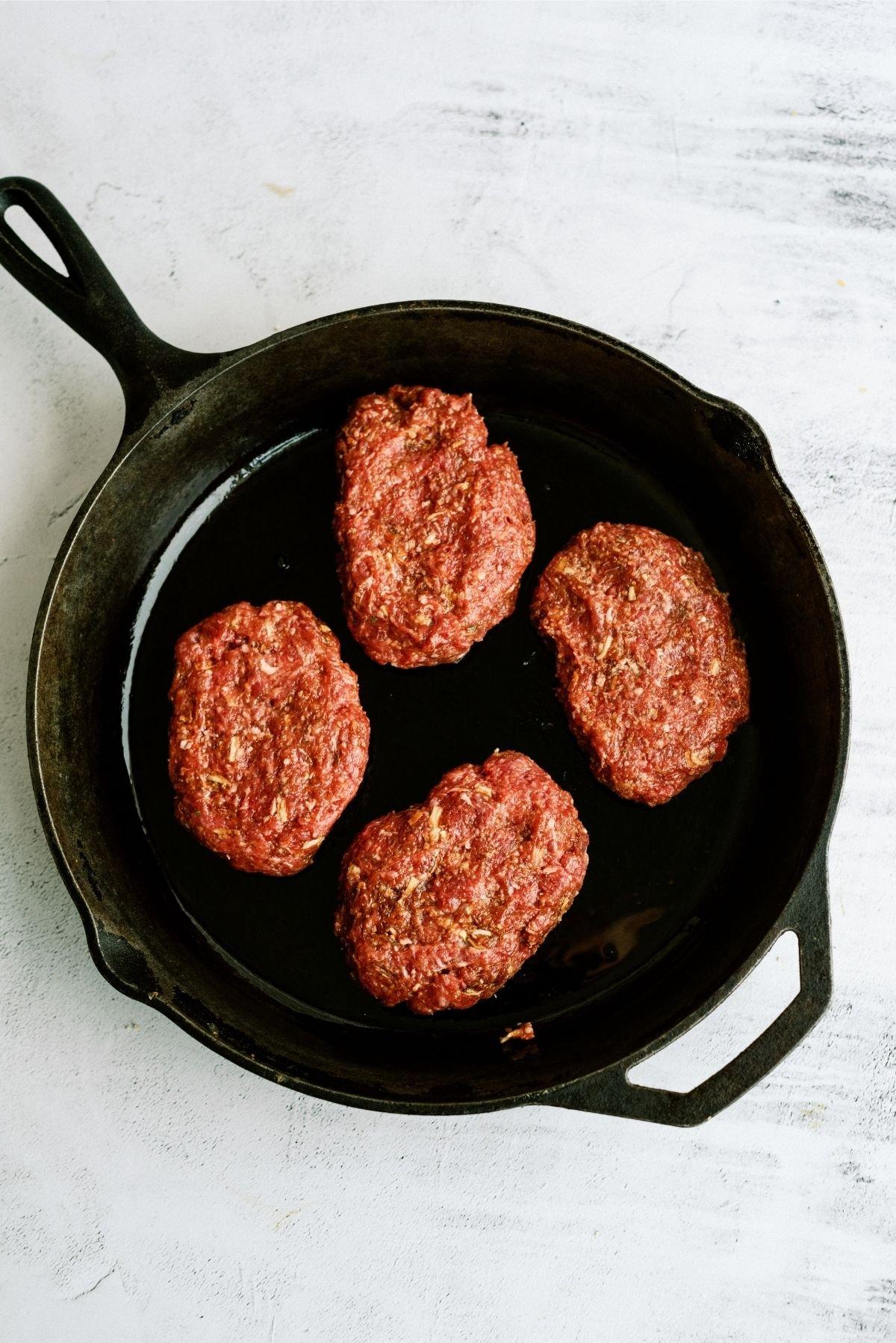 Skillet with 4 uncooked Salisbury Steak patties