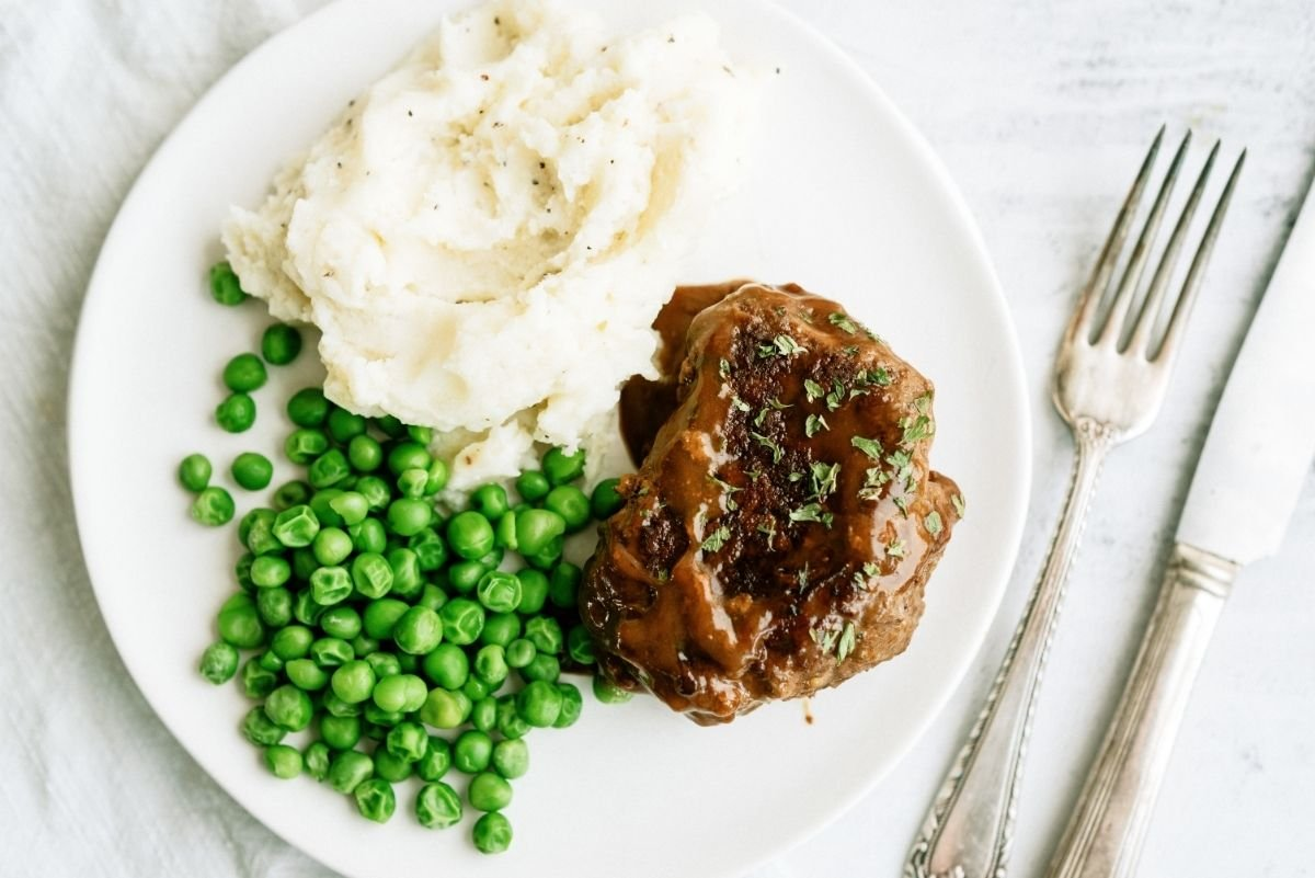 Salisbury Steak on a plate with mashed potatoes with green peas