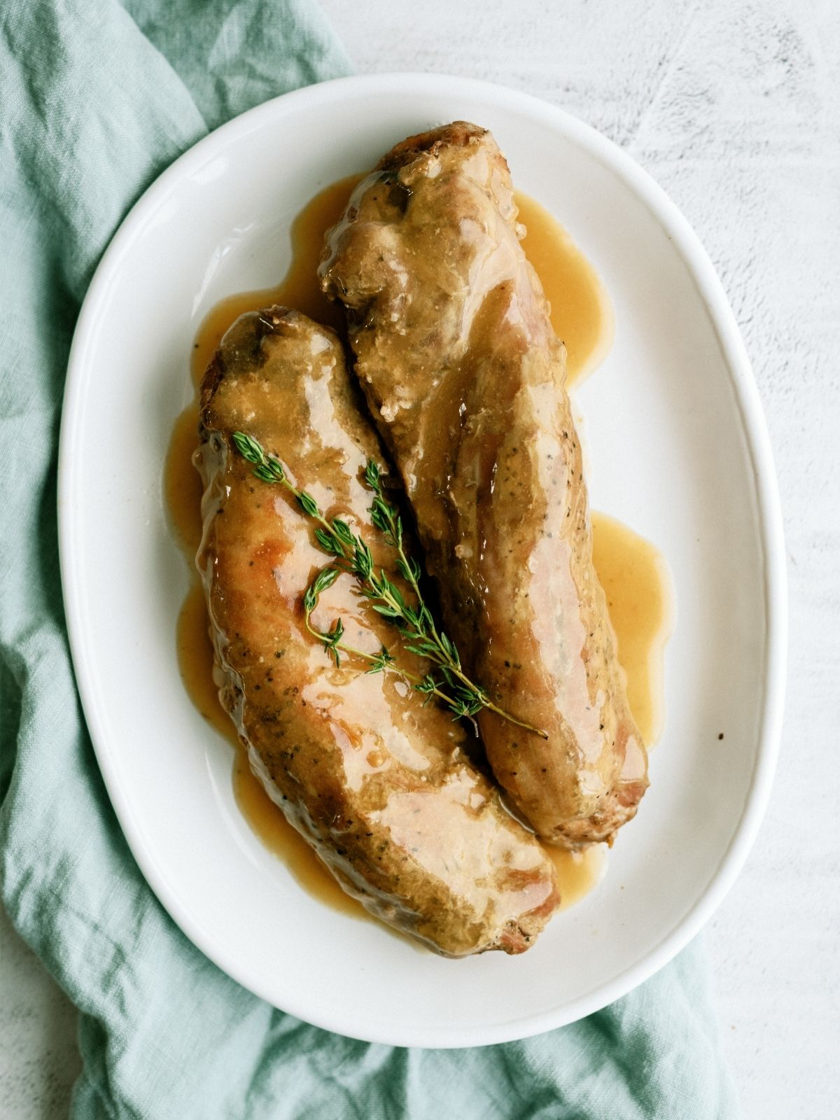 Slow Cooker Maple and Brown Sugar Pork Tenderloin on a serving plate with gravy.