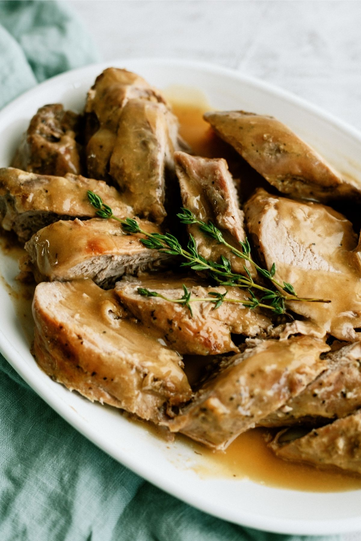 Slow Cooker Maple and Brown Sugar Pork Tenderloin sliced on a serving platter with gravy on top.