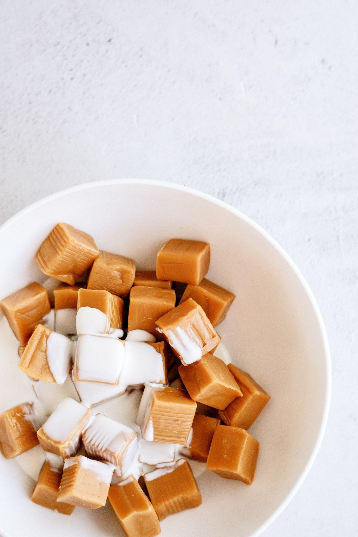 Caramels and evaporated milk in a microwave safe bowl