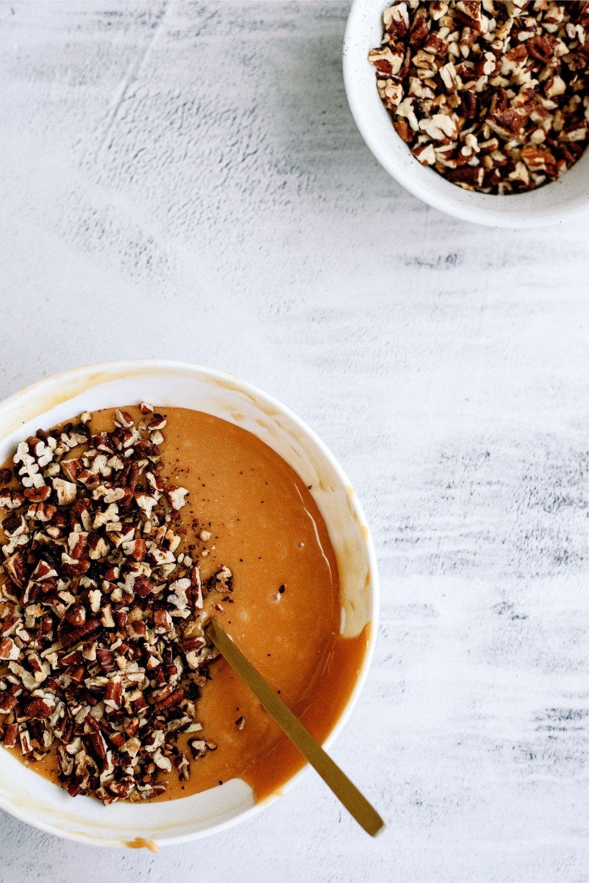 Pecans mixed in caramel sauce
