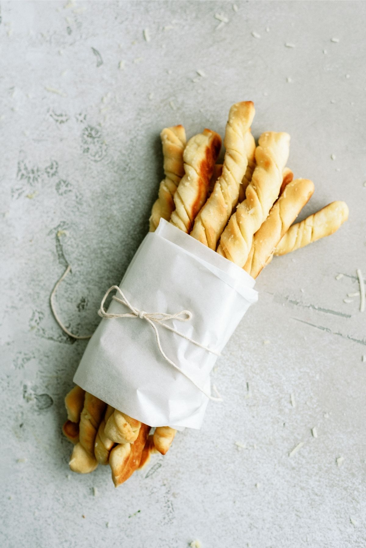 Homemade Pizza Factory Breadsticks wrapped with parchment paper and twine
