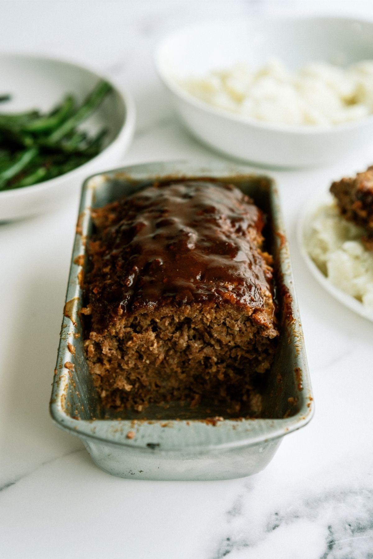 Honey BBQ Meatloaf in loaf pan sliced