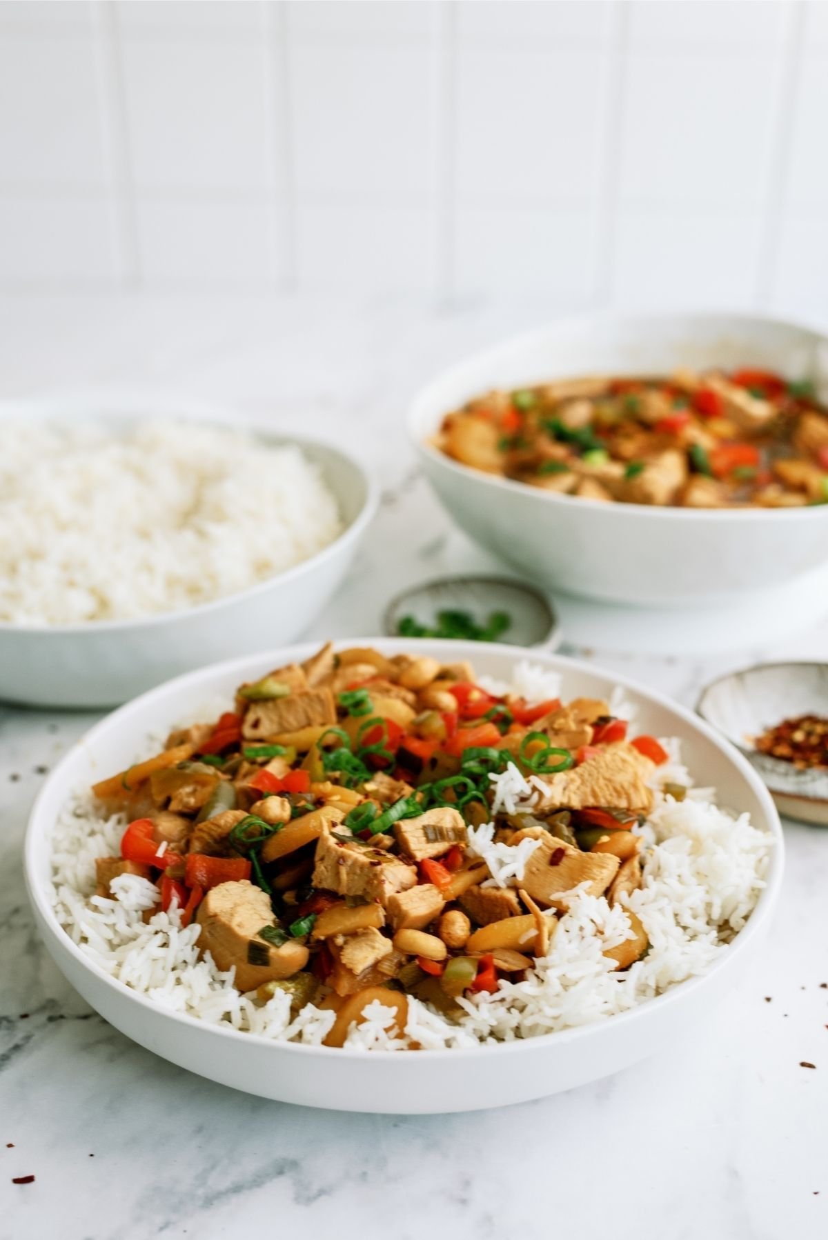 Slow Cooker Kung Pao Chicken in a white bowl served over rice