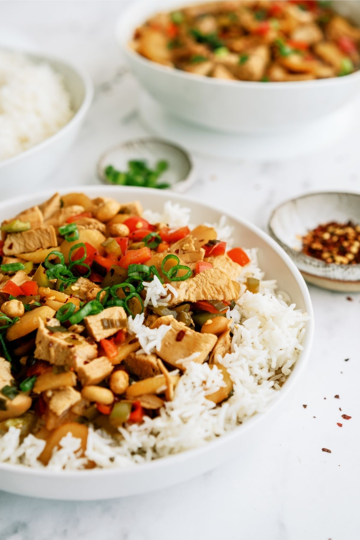 Slow Cooker Kung Pao Chicken served over rice in white bowl