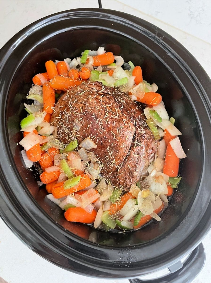 the perfect pot roast ready to cook in the slow cooker