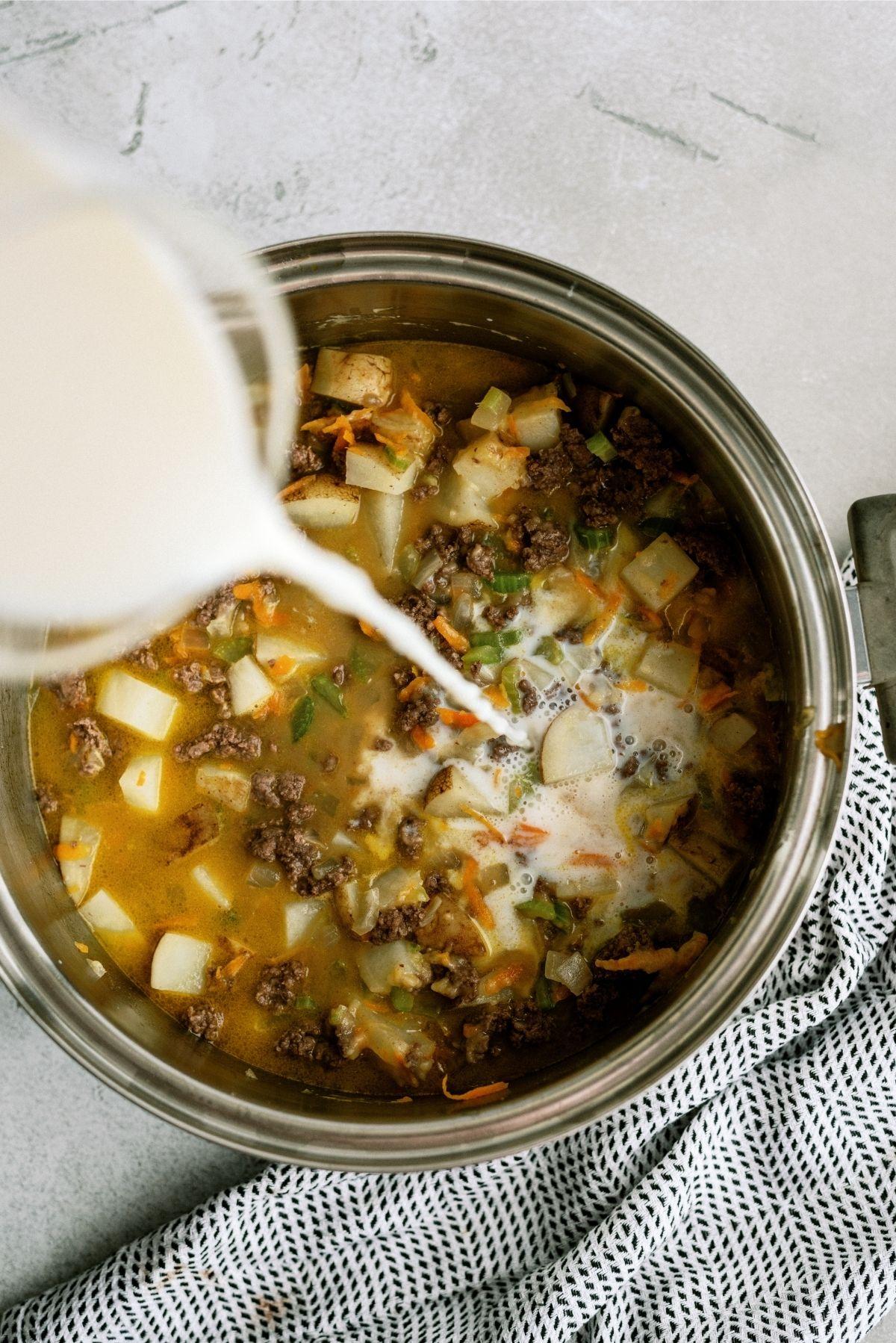 Adding milk to Cheeseburger Soup mixture in saucepan