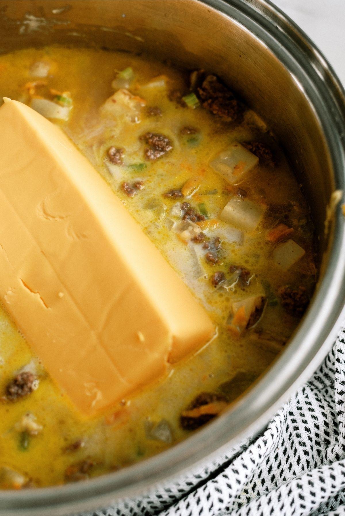 Adding brick of Velveeta cheese to saucepan full of Cheeseburger Soup
