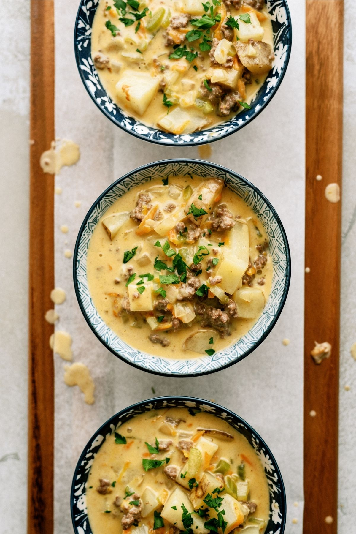 3 Bowls full of The Best Cheeseburger Soup Recipe (Cheesy Ground Beef Soup) on a wooden board