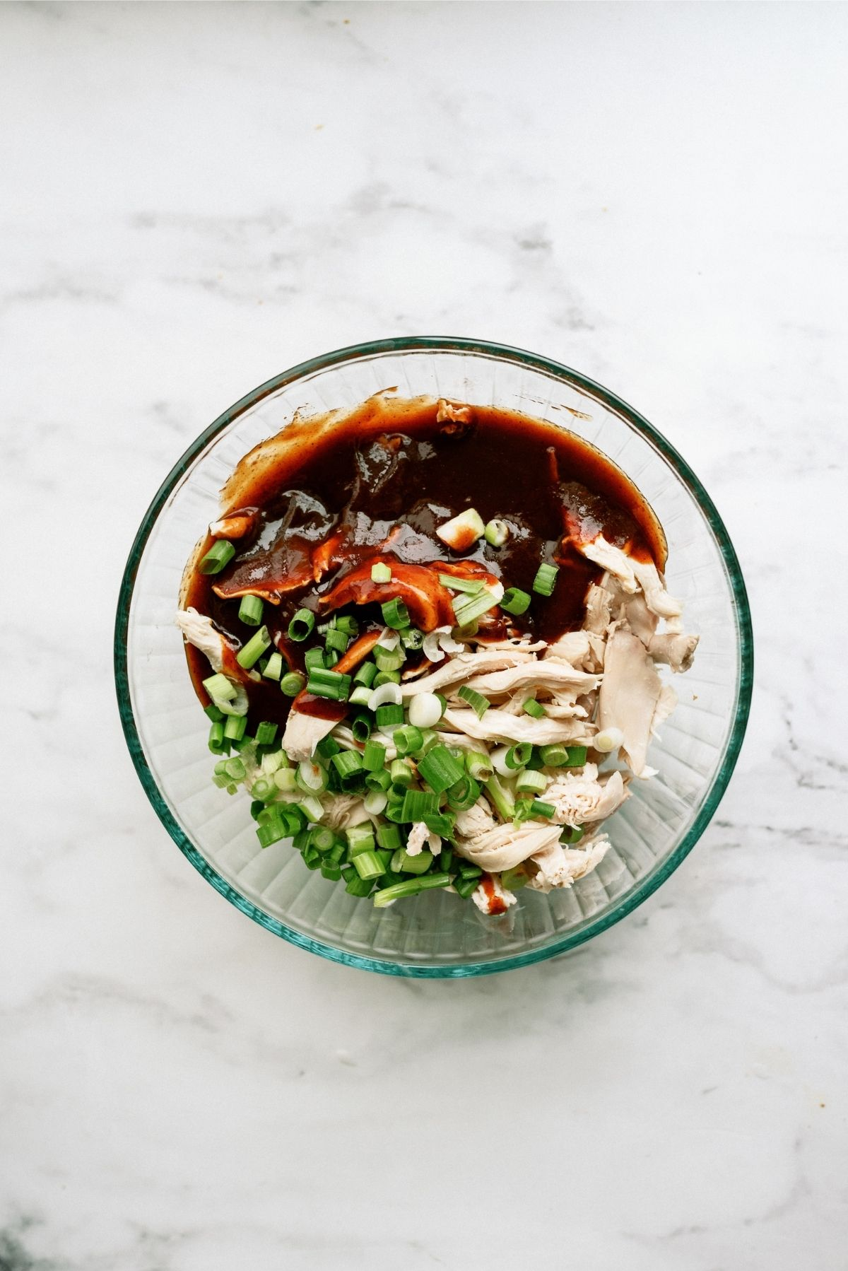 Chicken, BBQ sauce and green onions in a large mixing bowl