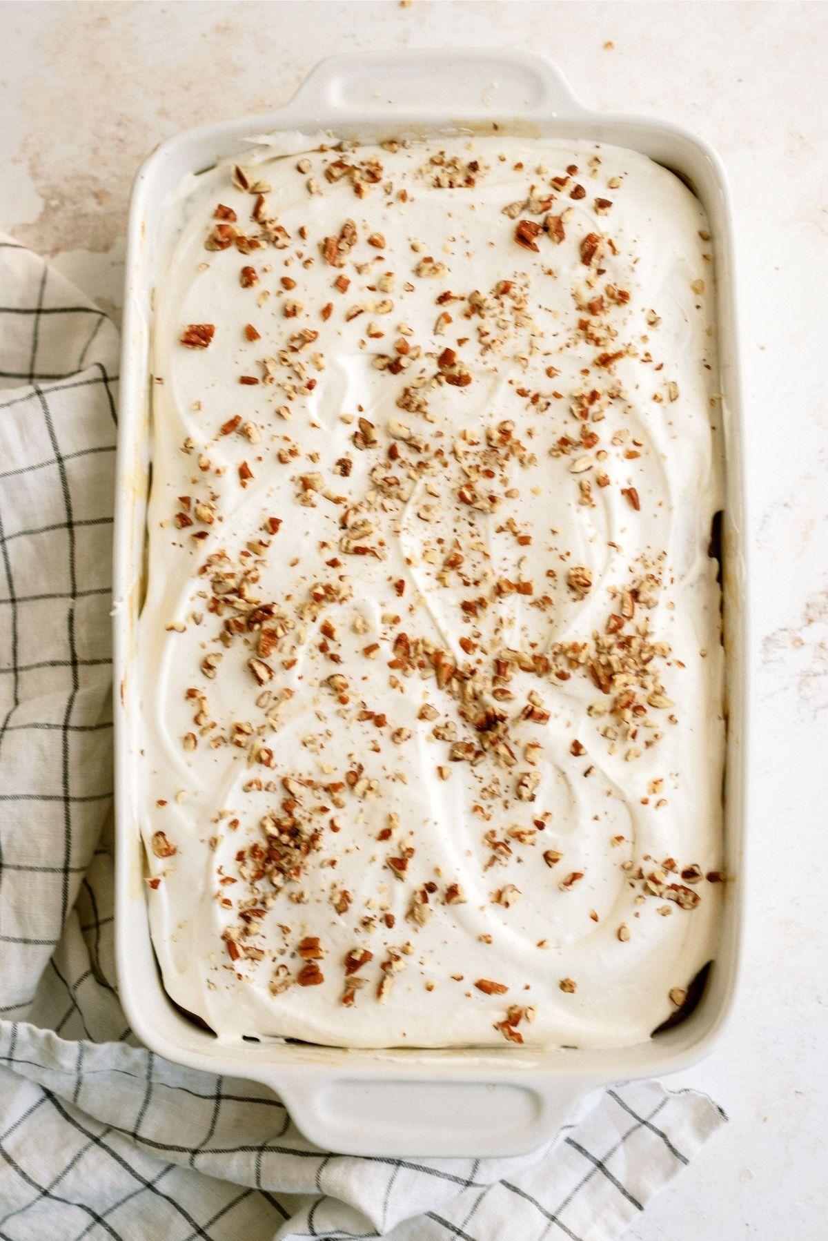 Caramel Pumpkin Poke Cake topped with chopped peacans in 9x13 pan