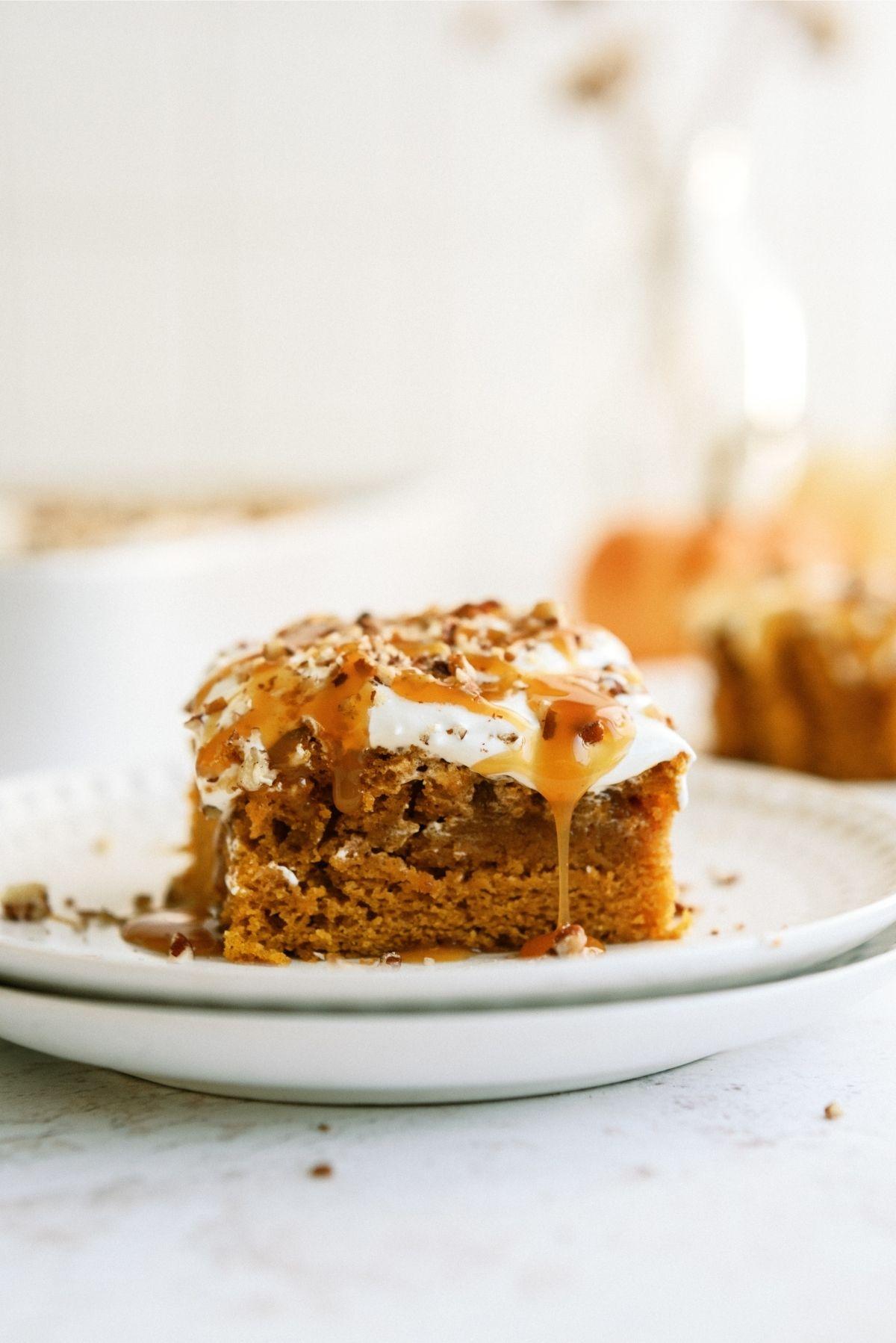 A slice of Caramel Pumpkin Poke Cake on a plate with cinnamon sticks