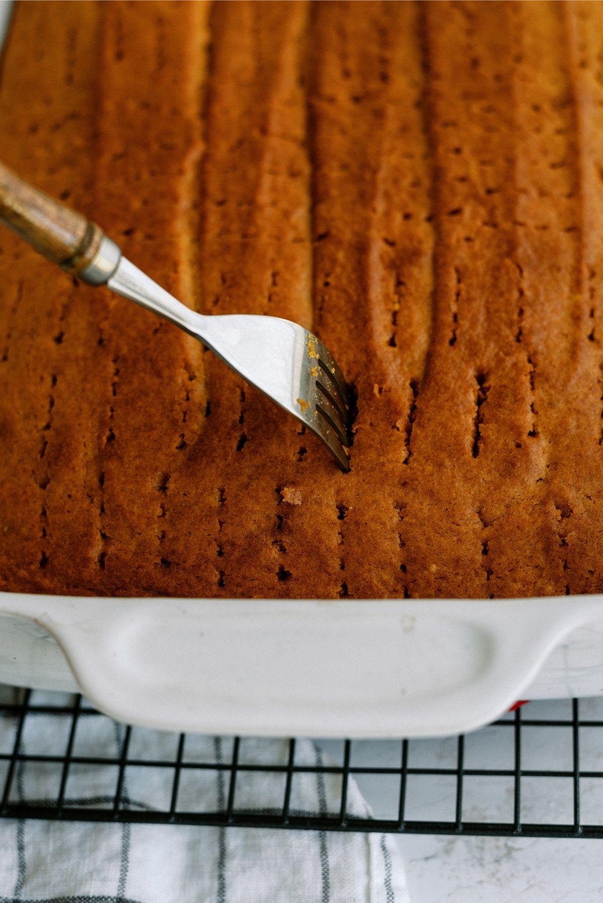 Fork poking holes in baked cake