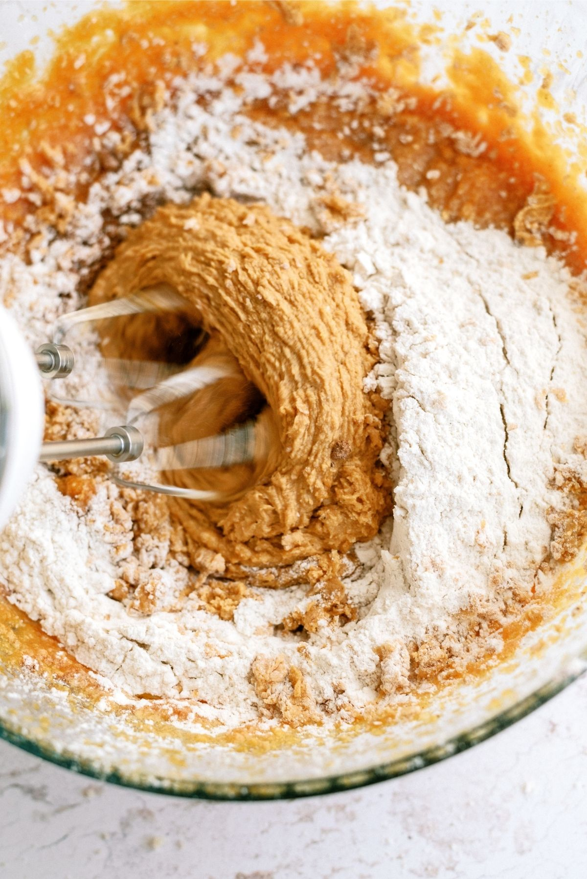 Dry ingredients added to wet ingredients and mixed with a hand mixer in a glass bowl